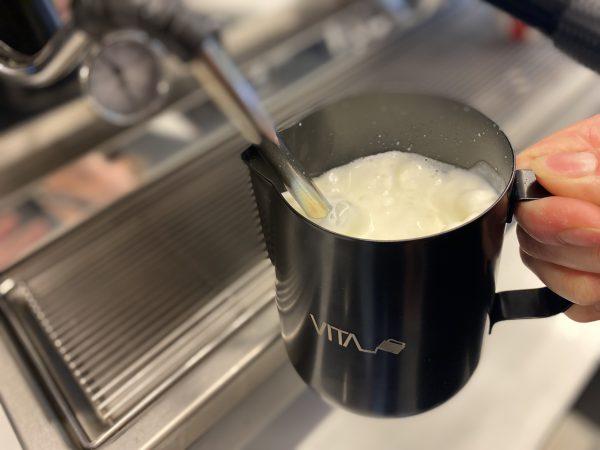 melk wordt opgeschuimd met stoompijpje